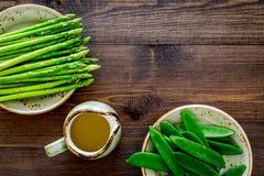 食物健康素食主义者 芦笋和豌豆在一个水罐油附近在黑暗的木背景顶视图copyspace 免版税图库摄影