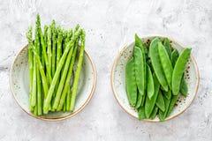 食物健康素食主义者 芦笋和豌豆在灰色石背景顶视图 免版税库存照片