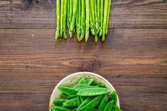 食物健康素食主义者 芦笋和豌豆在黑暗的木背景顶视图copyspace 免版税库存图片