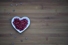 食物健康红色石榴种子的摄影图象在一个白色爱心脏形状盘的与木心脏形状装饰 库存照片