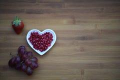 食物健康红色石榴种子的摄影图象在一个白色爱心脏形状盘的用在木背景的一个草莓 免版税图库摄影