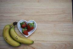 食物健康红色草莓的摄影图象在一个白色爱心脏形状盘的用在木背景的香蕉 免版税图库摄影