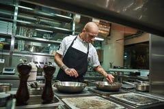 食物准备 有几纹身花刺的英俊和确信的厨师在他的油煎他的盘的胳膊成份在a 库存图片
