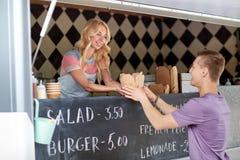 食物卡车服务男性顾客的女推销员 图库摄影