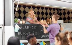 食物卡车服务男性顾客的女推销员 库存照片