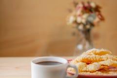 食物和点心 有裂痕的酥脆曲奇饼用在板材和一杯咖啡的糖在一张木桌上的 免版税图库摄影