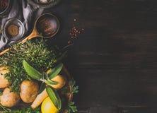 食物和烹调背景与菜,味道草本和烹调匙子在黑暗的土气背景,顶视图 库存照片