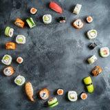 食物圆的框架由套日本食物制成在黑暗的背景 寿司卷、nigiri、未加工的鲑鱼排、米和鲕梨 平的la 库存图片