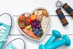 食物在心脏和哑铃健身摘要健康生活方式概念里 免版税库存图片
