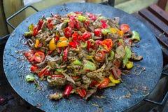 食物在格栅的牛肉bbq与火服务用蕃茄和烘烤菜 免版税库存图片
