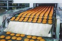 食物工厂、工业传送带或者线与甜曲奇饼、面包店和食物生产概念的准备的过程 免版税库存照片