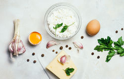 食物有机成份:酸奶干酪 鸡蛋、大蒜和荷兰芹在白色土气具体背景 顶视图,平的位置 库存照片