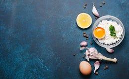 食物有机成份:酸奶干酪 鸡蛋、大蒜和荷兰芹在黑暗的背景 顶视图,平的位置 免版税库存照片