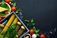 食物框架意大利食物背景 健康食物概念或成份烹调的pesto调味汁在黑暗的背景 顶视图机智 免版税库存照片