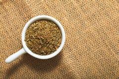 食物概念加香料在白色陶瓷杯子的小茴香籽在棕色麻袋布背景 免版税库存照片