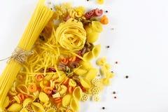 食物概念-各种各样的未煮过,未加工的意大利面团,在白色背景,顶视图,文本的,集合地方的被涂的胡椒豌豆 库存照片