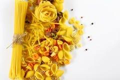 食物概念-各种各样的未煮过,未加工的意大利面团,在白色背景,顶视图,文本的,集合地方的被涂的胡椒豌豆 免版税库存照片