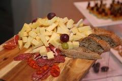 食物照片被切的和立即可食的品种:不同的种类乳酪、被治疗的火腿、抽烟的香肠、葡萄和面包 免版税库存图片