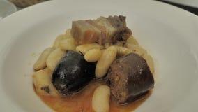 食物的关闭:全国北西班牙盘:Fabada,在一块圆的白色板材 股票录像