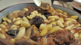 食物的关闭:全国北西班牙盘:Fabada,在一块圆的白色板材 股票视频
