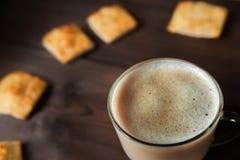 食物的开胃图片,一个杯子用芬芳咖啡,上等咖啡,反对一张黑暗的木桌的牛奶特写镜头 咖啡泡沫结构  免版税库存照片