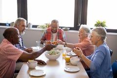 给食物的老人坐在桌上的朋友 免版税图库摄影