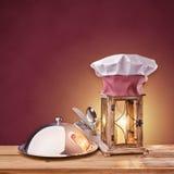 食物盘子、盖帽厨师和灯笼在红色背景 免版税库存照片