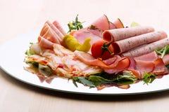 食物盘子用可口切的火腿蒜味咸腊肠、片断,香肠、蕃茄、沙拉和菜- 图库摄影
