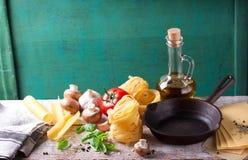 食物背景或健康概念与橄榄油,新鲜的蓬蒿,面团tagliatelle,蘑菇,蕃茄,胡椒和烹调平底锅 免版税库存图片