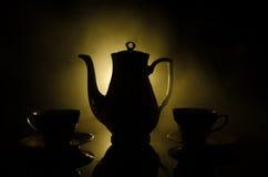 食物背景茶和咖啡题材 老有杯子水罐和糖杯子的葡萄酒陶瓷茶或咖啡罐在与锂的黑暗的背景 免版税库存照片