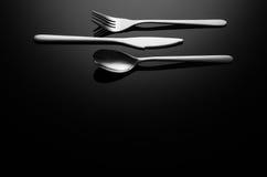 黑食物背景,反射性表面上的银器与拷贝空间 库存图片