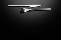 黑食物背景,反射性表面上的银器与拷贝空间 免版税库存图片