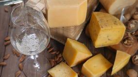 食物艺术 不同的类乳酪在木背景美妙地安排了 顶视图 白葡萄酒涌入 股票录像