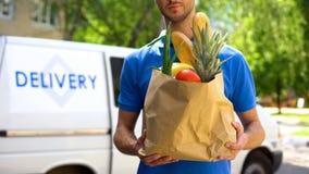 食物送货服务,男性工作者藏品食品杂货袋,明确食物命令 免版税库存图片