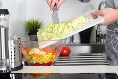 食物,家庭,烹调和人概念-在厨房里供以人员砍在切板的一棵圆白菜有刀子的 库存图片