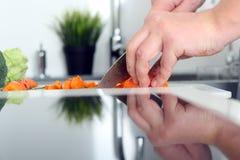 食物,家庭,烹调和人概念-在厨房里供以人员砍在切板的一棵红萝卜有刀子的 库存图片