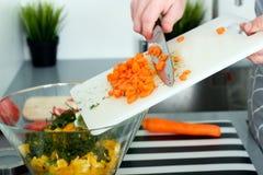 食物,家庭,烹调和人概念-在厨房里供以人员砍在切板的一棵红萝卜有刀子的 免版税图库摄影