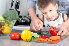 食物,家庭,烹调和人概念-在有儿子的厨房里供以人员砍在切板的辣椒粉有刀子的 免版税库存图片