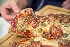 食物,意大利厨房和吃光概念-接近采取和分享在木桌上的手自创薄饼 免版税库存照片