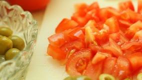 食物 切片蕃茄和在白色切板的绿橄榄菜 免版税库存照片