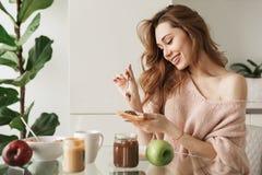 食用一个微笑的少妇的画象鲜美早餐 免版税库存图片
