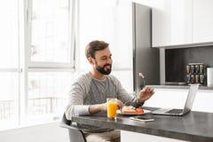 食用一个微笑的年轻的人的画象早餐 免版税库存图片