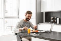 食用一个快乐的年轻的人的画象早餐 免版税库存图片