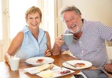 食用一对美好的资深的夫妇的画象早餐一起 免版税库存图片