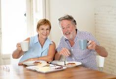 食用一对美好的资深的夫妇的画象早餐一起 库存图片