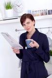 食用一杯茶和读报纸的妇女 免版税库存图片