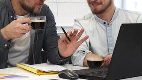 食用两个男性企业的同事播种的射击谈论的咖啡工作 库存照片