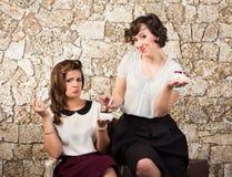 食用两个美丽的女朋友茶 免版税库存图片