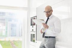 食用中间成人的商人咖啡,当在家时读报纸 免版税图库摄影