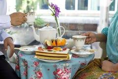 食用亚裔的商人茶和蛋糕和新鲜水果 免版税库存照片